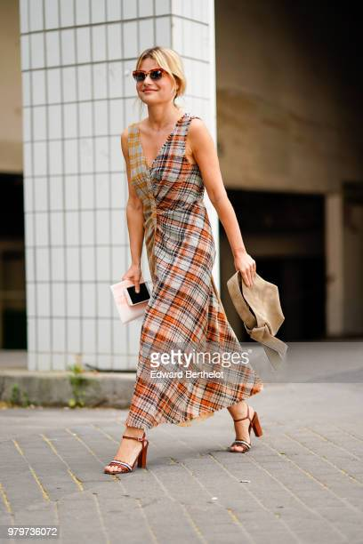 A guest wears a tartan checked dress outside Acne during Paris Fashion Week Menswear SpringSummer 2019 on June 20 2018 in Paris France