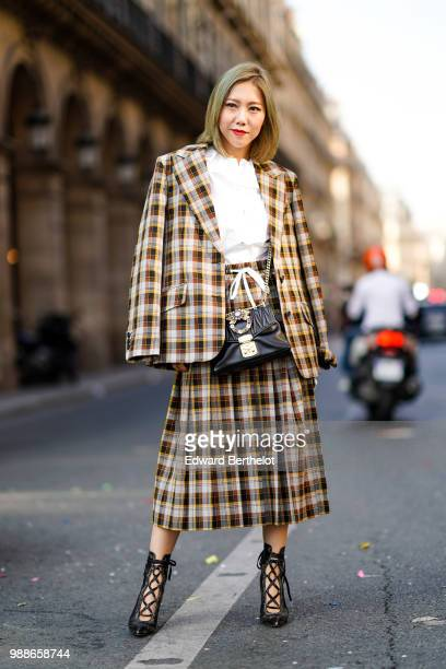 A guest wears a tartan checked pattern brown blazer jacket a white top a black bag a pleated skirt outside the Miu Miu Cruise Collection show outside...