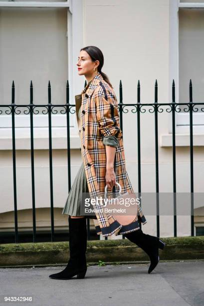 A guest wears a tartan checked trench coat a pleated dress a pink semi circular bag black thigh high boots during London Fashion Week February 2018...