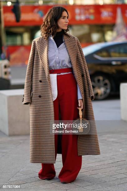 A guest wears a tartan checkered long coat a striped shirt red pants a Vuitton circular bag a black turtleneck outside Louis Vuitton during Paris...