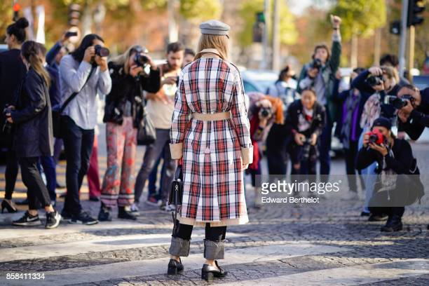 A guest wears a tartan coat poses in front of photographers outside Chanel during Paris Fashion Week Womenswear Spring/Summer 2018 on October 3 2017...