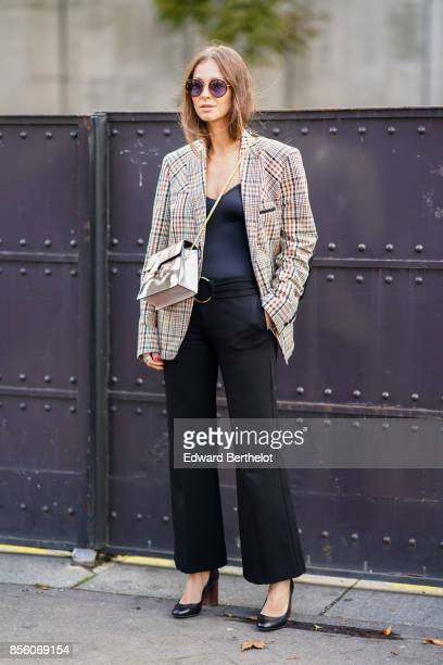 A guest wears a tartan jacket a black top black flare pants outside Mugler during Paris Fashion Week Womenswear Spring/Summer 2018 on September 30...