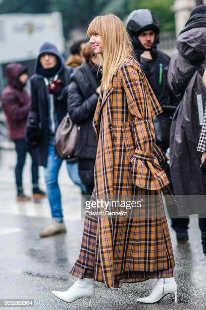 A guest wears a tawny plaid maxi trenchcoat with flare sleeves white pointy toe highheeled boots outside Balmain during Paris Fashion Week Womenswear...