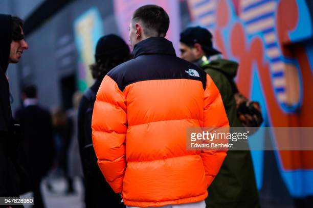A guest wears a 'The North face' orange puffer jacket during London Fashion Week Men's January 2018 at on January 6 2018 in London England
