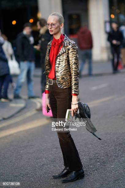 A guest wears a tiger shiny print jacket a red top flare pants during London Fashion Week February 2018 on February 17 2018 in London England