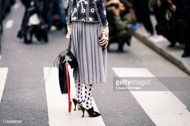 A guest wears a top with red anchors embroidered on the cuffs a beaded navy blue jacket with white anchors design a grey pleated skirt a black bag...