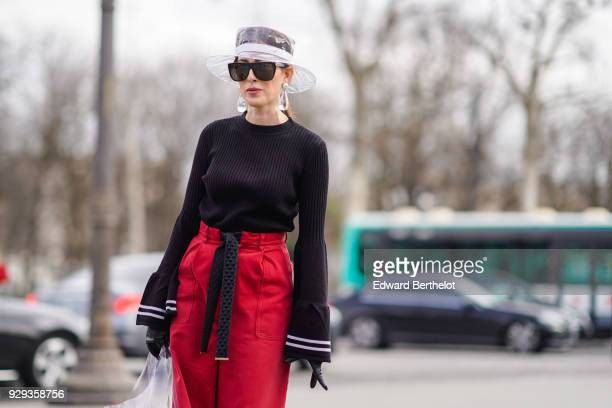 A guest wears a transparent hat sunglasses a balck top with flared sleeves  red pants outside a7a6dbc6260
