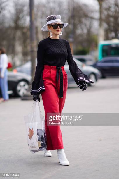 048d4dacbdb A guest wears a transparent hat sunglasses a black top red flare pants  white shoes a