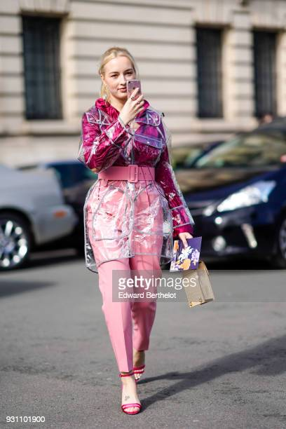 A guest wears a transparent plastic trench coat a fuchsia shirt pink pants and a large pink belt pink sandals and a beige handbag during Paris...