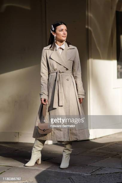 A guest wears a trench coat a bag boots pearl earrings during London Fashion Week February 2019 on February 17 2019 in London England