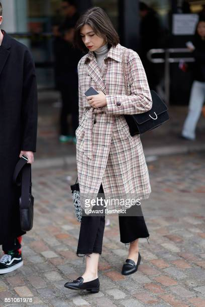 A guest wears a trench coat a bag cropped pants black shoes outside Preen by Thornton Bregazzi during London Fashion Week September 2017 on September...
