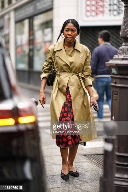 Guest wears a trench coat, a black and red floral print dress, black shoes, a bag, outside Ralph & Russo, during Paris Fashion Week - Womenswear...