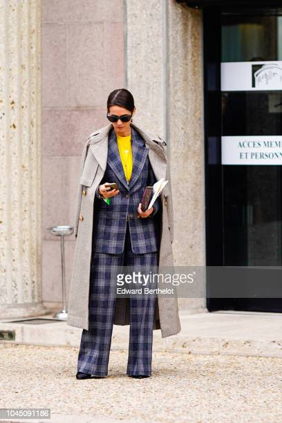 A guest wears a trench coat a checked blazer jacket flare pants a yellow top outside Miu Miu during Paris Fashion Week Womenswear Spring/Summer 2019...