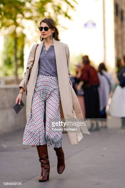 Guest wears a trench coat, a gray top, checked pants, brown leather boots, outside Haider Ackermann, during Paris Fashion Week Womenswear...