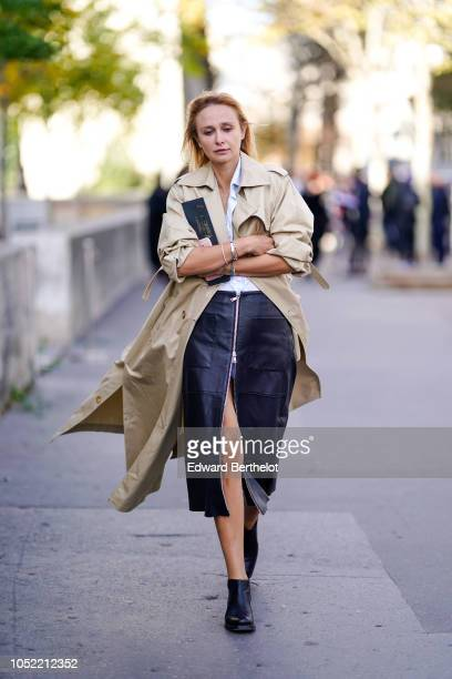 A guest wears a trench coat a leather skirt black shoes outside Haider Ackermann during Paris Fashion Week Womenswear Spring/Summer 2019 on September...