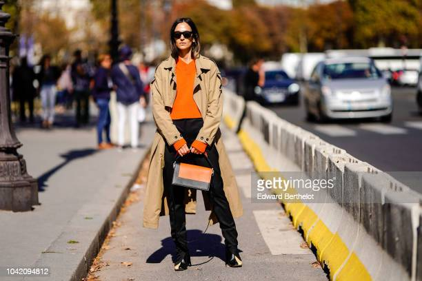 A guest wears a trench coat an orange pullover an orange bag black pants sunglasses outside Paco Rabanne during Paris Fashion Week Womenswear...