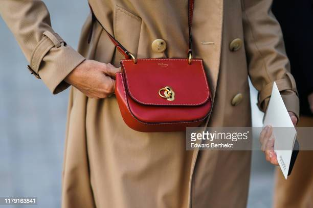 Guest wears a trench coat and a red Mulberry bag, outside Louis Vuitton, during Paris Fashion Week - Womenswear Spring Summer 2020, on October 01,...