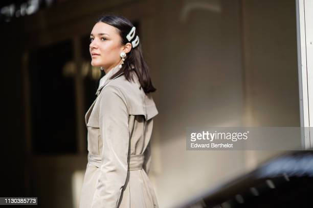 A guest wears a trench coat boots pearl earrings a hair brooch during London Fashion Week February 2019 on February 17 2019 in London England