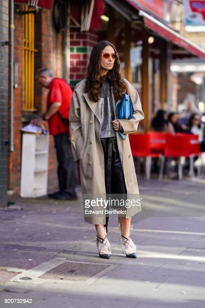 A guest wears a trench coat sunglasses a blue bag black shoes a black leather skirt during London Fashion Week February 2018 on February 17 2018 in...