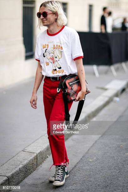 A guest wears a tshirt with red lining red pants red sunglasses a bag converse sneakers shoes outside the Valentino show during Paris Fashion Week...