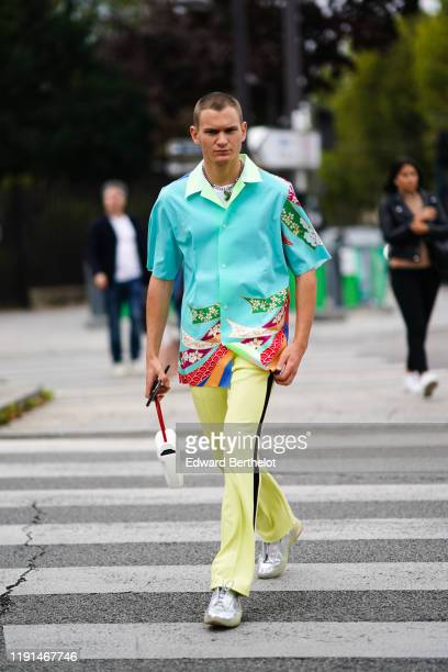 Guest wears a turquoise shirt with floral print, yellow pants, sneakers, a white bag, outside Ann Demeulemeester, during Paris Fashion Week -...