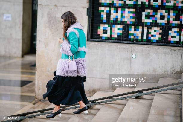 A guest wears a turquoise suede coat with pale violet inserts a black lustrous flowy and flounced long skirt a pale violet handbag black pumps with...