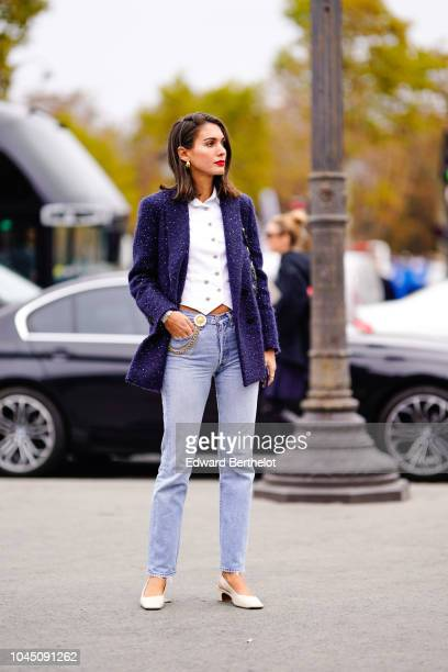 A guest wears a tweed blue jacket a white shirt pale blue denim jeans white shoes outside Chanel during Paris Fashion Week Womenswear Spring/Summer...