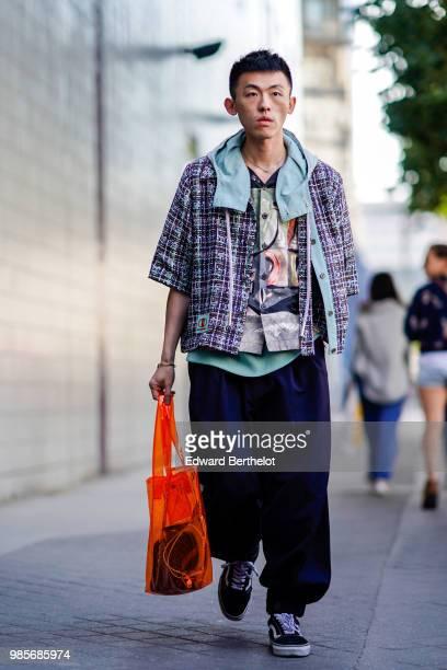 A guest wears a tweed jacket large blue pants sneakers outside 1017 ALYX 9SM during Paris Fashion Week Menswear SpringSummer 2019 on June 24 2018 in...