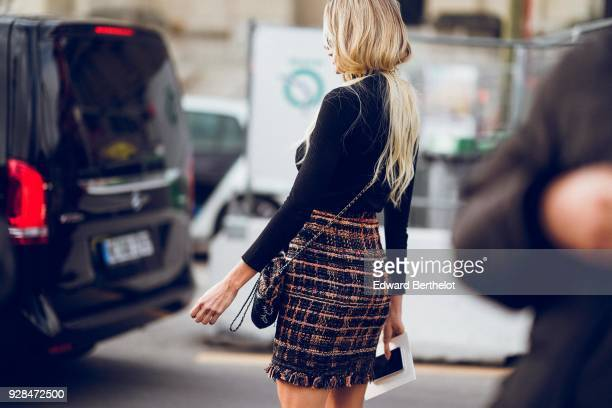 A guest wears a tweed skirt outside Chanel during Paris Fashion Week Womenswear Fall/Winter 2018/2019 on March 6 2018 in Paris France