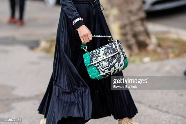 A guest wears a Valentino bag with a printed tiger face outside Valentino during Paris Fashion Week Womenswear Spring/Summer 2019 on September 30...