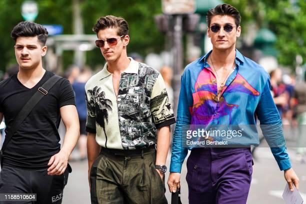A guest wears a vneck black top black sport pants A guest wears sunglasses a creamcolor and black landscape print frontzip shirt lustrous brown pants...
