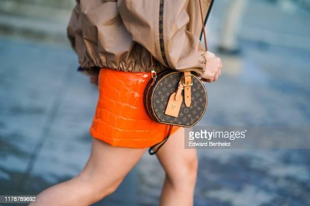 Guest wears a Vuitton monogram logo Small Hat Box bag, an orange crocodile pattern leather skirt outside Louis Vuitton, during Paris Fashion Week -...