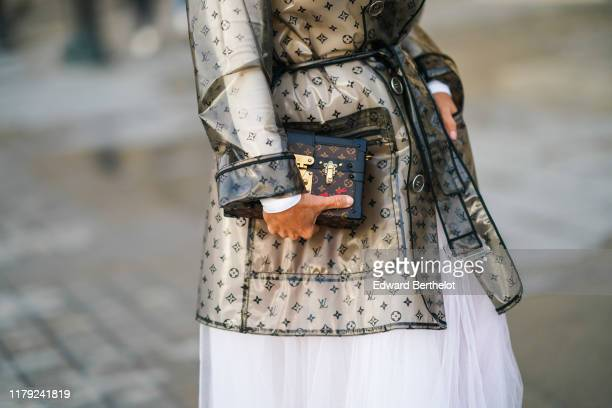 A guest wears a Vuitton plastic clear rain coat and a Vuitton rigid Petite Malle bag outside Louis Vuitton during Paris Fashion Week Womenswear...