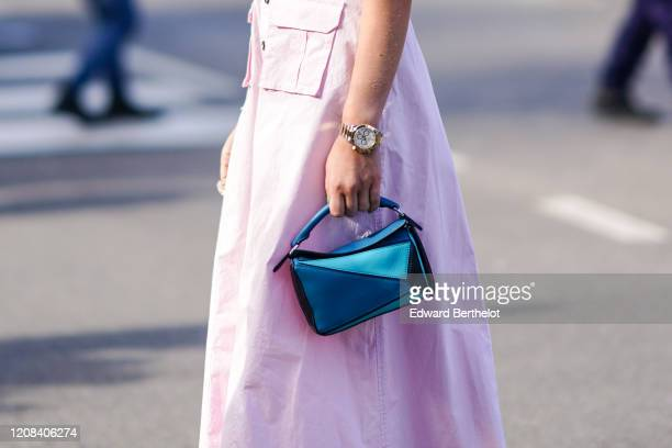 Guest wears a watch, a pink dress, a blue Loewe bag, outside BOSS, during Milan Fashion Week Fall/Winter 2020-2021 on February 23, 2020 in Milan,...