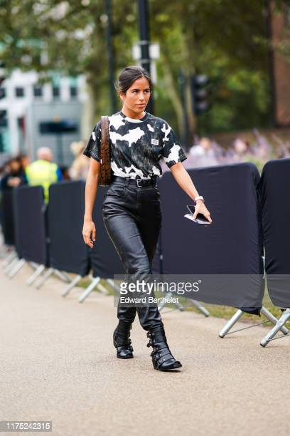 Guest wears a white and black cowhide pattern top, a black belt, black leather pants, black strappy open-toe boots, a brown python pattern bag,...