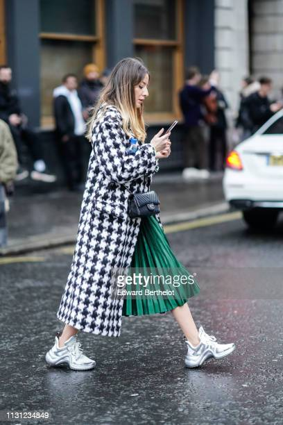 A guest wears a white and black houndstooth coat a black Chanel bag a shiny green pleated skirt white and silver Louis Vuitton sneakers during London...