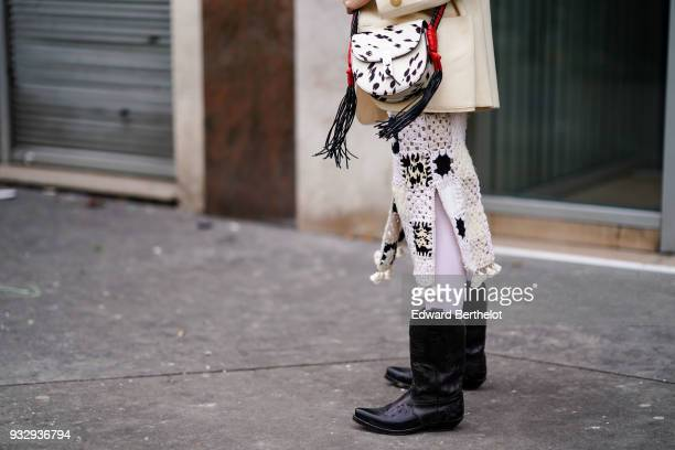 A guest wears a white and black spotted hand bag a tasselslined white crochet skirt with black patterns black cowboy boots during Paris Fashion Week...