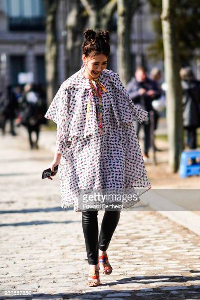 A guest wears a white and brown flowy flounced and flared tunic with a multicolor tie glossy black leggings multicolor sandals during Paris Fashion...
