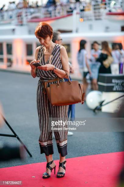 A guest wears a white and brown striped wrapover jumpsuit a brown belt a brown bag black heeled sandals outside the Kerastase Party At Port Debilly...