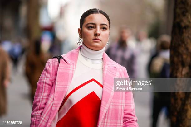 A guest wears a white and orange turtleneck a pink checkered coat earrings during London Fashion Week February 2019 on February 19 2019 in London...