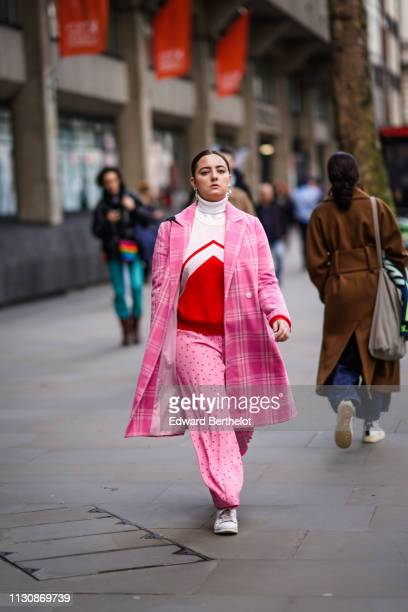 A guest wears a white and orange turtleneck a pink checkered coat pink fluid pants with red polka dots white sneakers during London Fashion Week...
