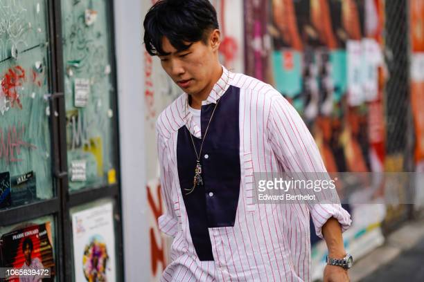 A guest wears a white and pink striped shirt outside Yohji Yamamoto during Paris Fashion Week Menswear SpringSummer 2019 on June 21 2018 in Paris...