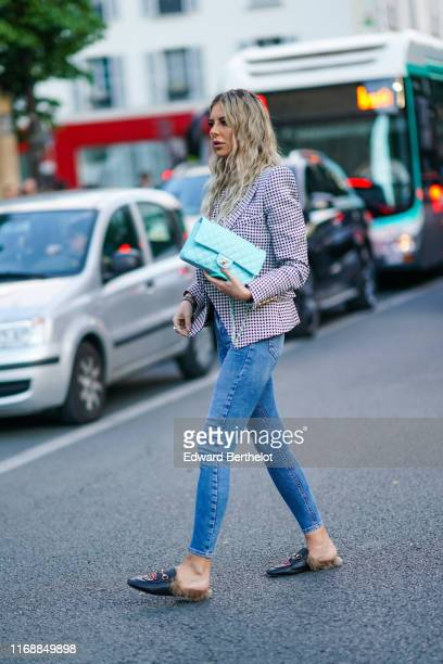Guest wears a white and purple houndstooth jacket, a turquoise blue Chanel bag, skinny jeans, navy blue slippers with fur, outside Balmain, during...