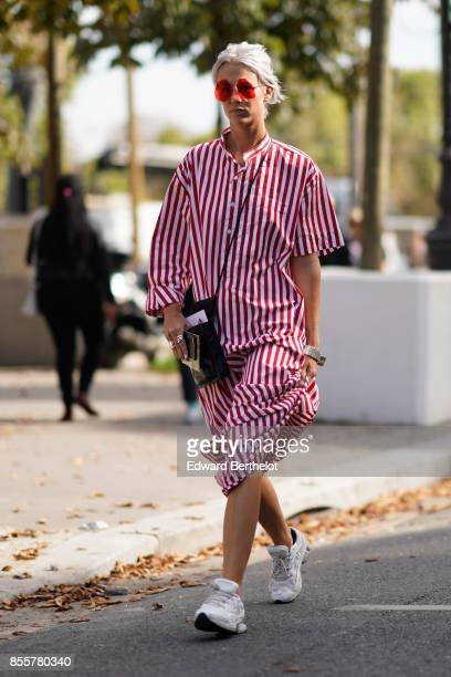 A guest wears a white and red striped dress outside Issey Miyake during Paris Fashion Week Womenswear Spring/Summer 2018 on September 29 2017 in...