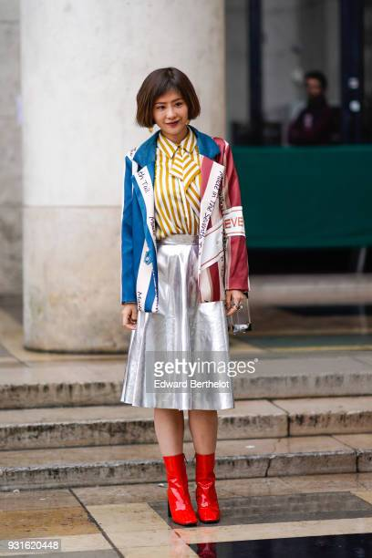 A guest wears a white and yellow striped shirt a multicolor jacket a silver shiny skirt red pvc shoes during Paris Fashion Week Womenswear...