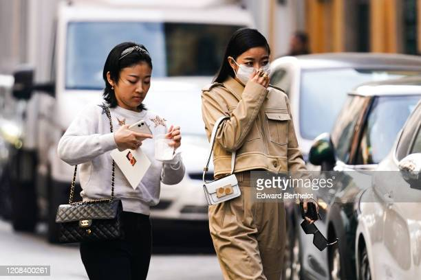 A guest wears a white bag a pale brown jacket a face mask outside BOSS during Milan Fashion Week Fall/Winter 20202021 on February 23 2020 in Milan...