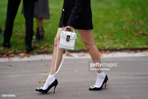 A guest wears a white bag white ankle socks black stilettos with rhinestones outside the Rochas show during Paris Fashion Week Womenswear...