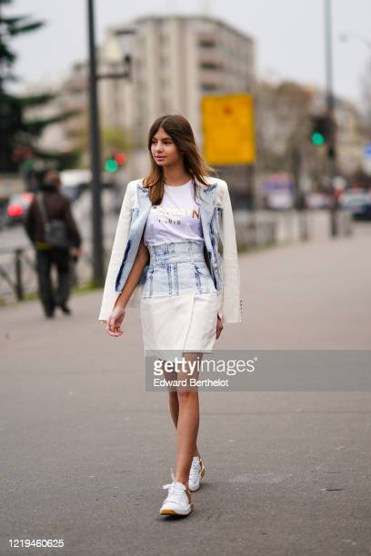 Guest wears a white Balmain top , a cream-color and washed-out denim jacket, a matched wrap mini skirt with a high waist, white and gold-tone Balmain...