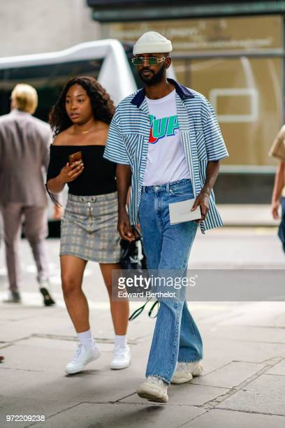 A guest wears a white beanie hat a striped shirt a 7'UP tshirt blue jeans sneakers sunglasses during London Fashion Week Men's June 2018 on June 09...