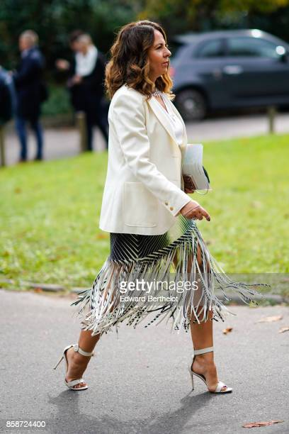 A guest wears a white blazer jacket a fringe dress white heels outside Leonard during Paris Fashion Week Womenswear Spring/Summer 2018 on October 2...